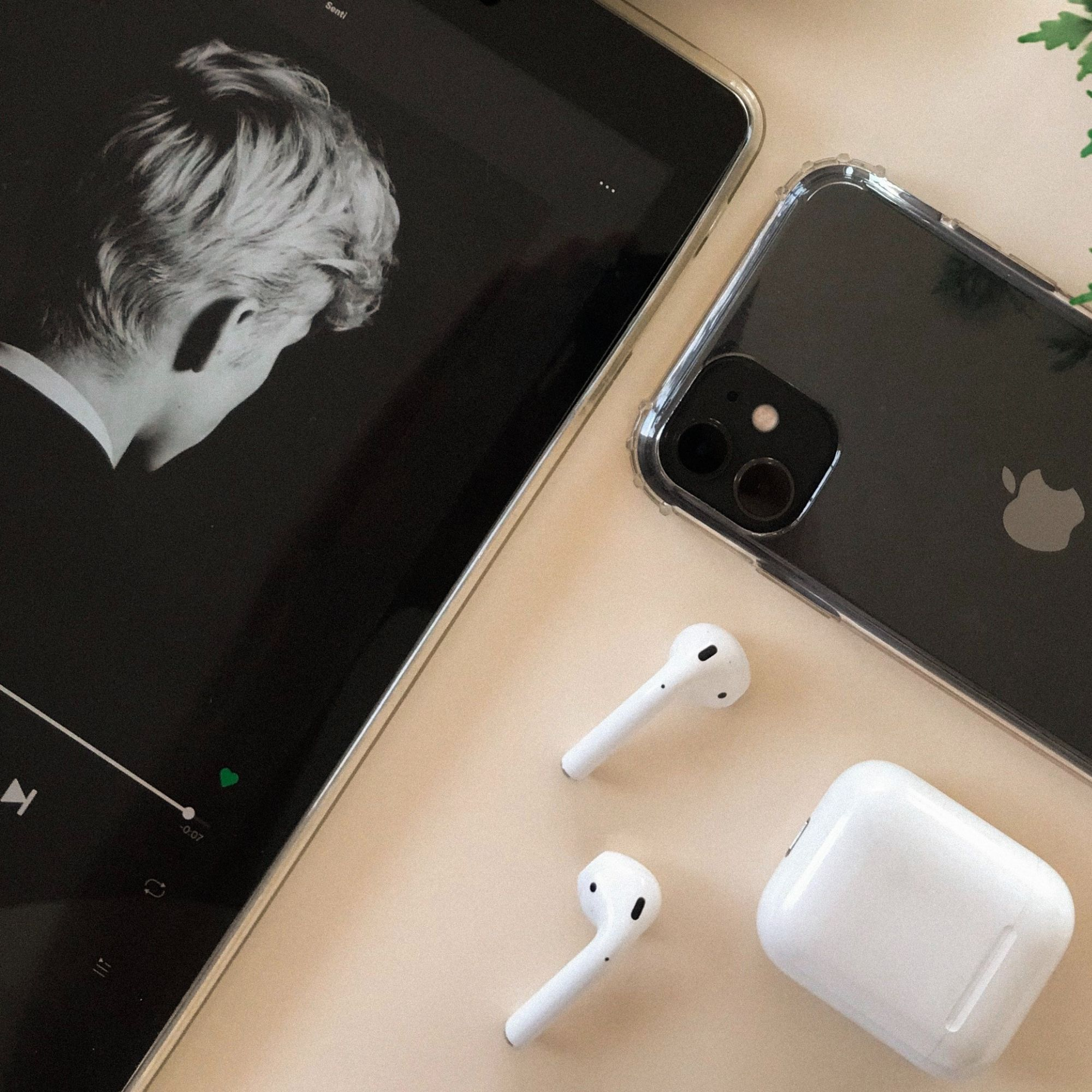 Apple products (airpods, iphone) stylized on table