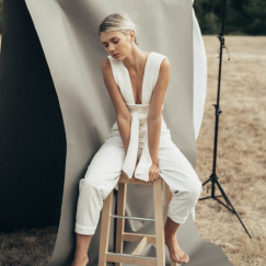 Woman in white sitting on stool