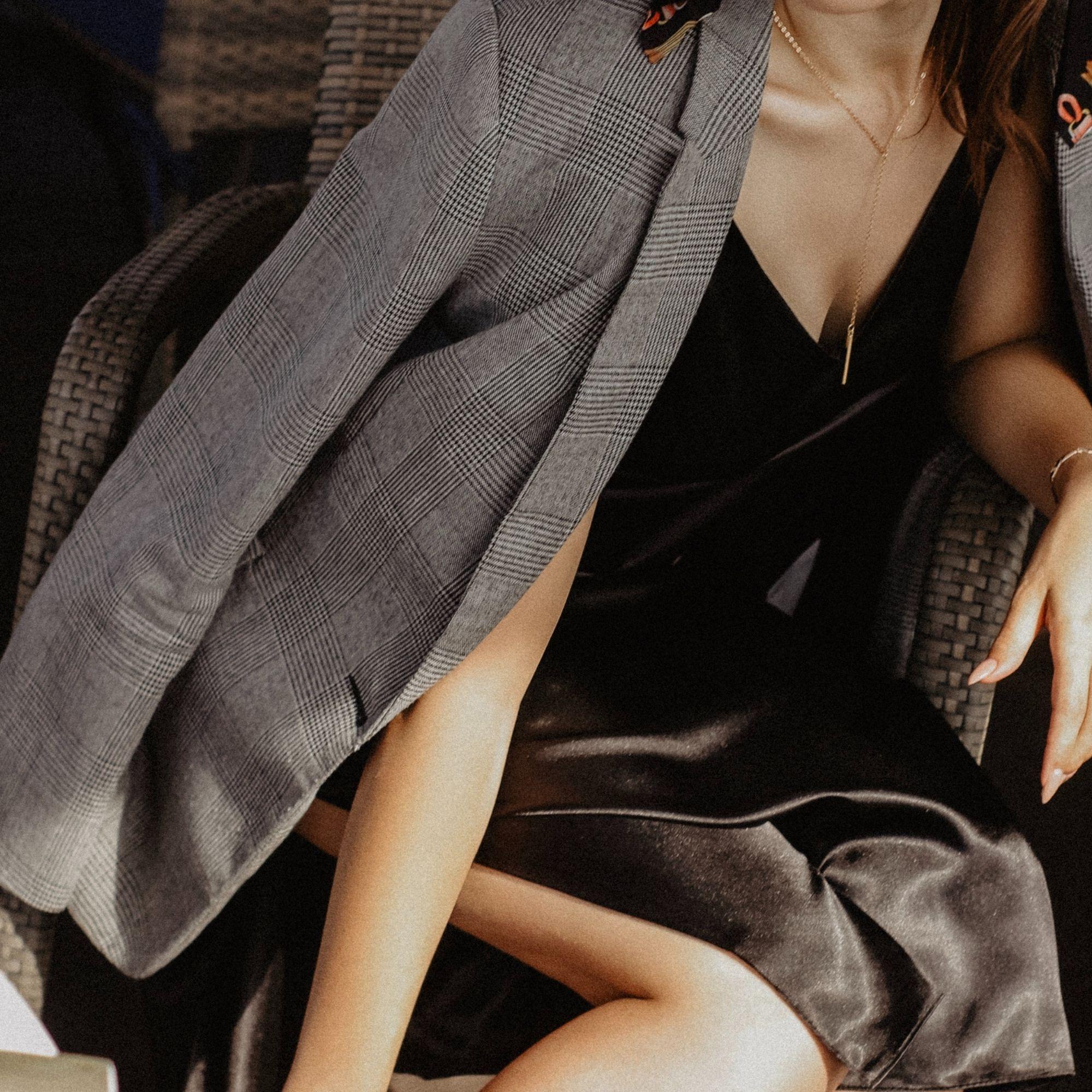 Woman in grey blazer and black slip dress