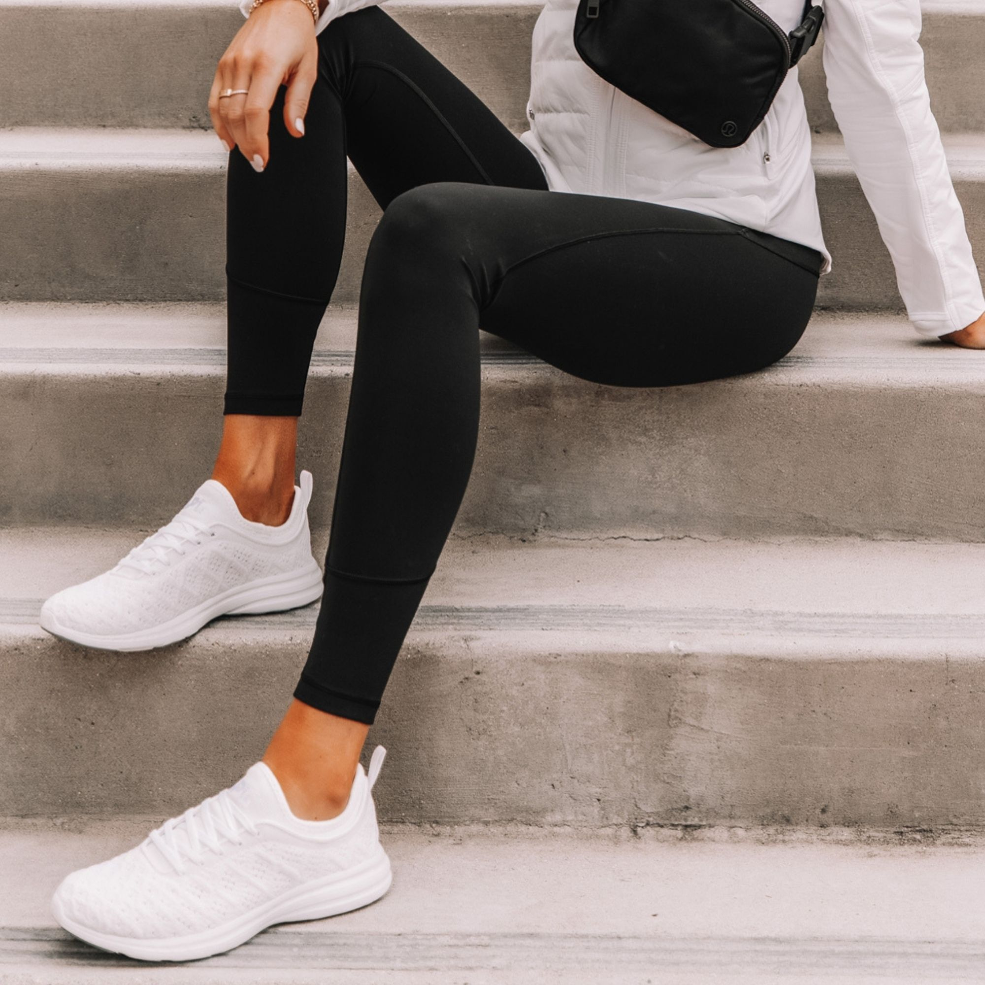 White sneakers with black leggings on woman