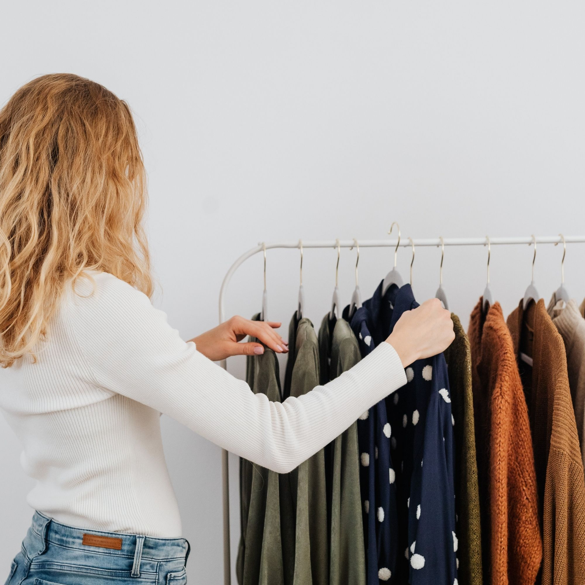 Woman picking out a polka dot clothing from rack
