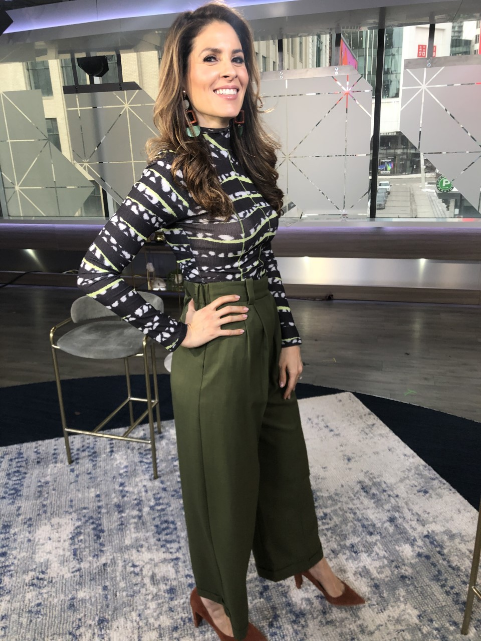 Dina wearing army green wide leg trousers with black and white top