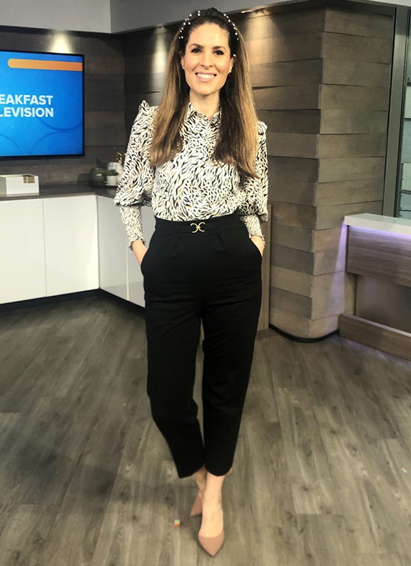 Dina wearing black ankle tapered pants with blouse