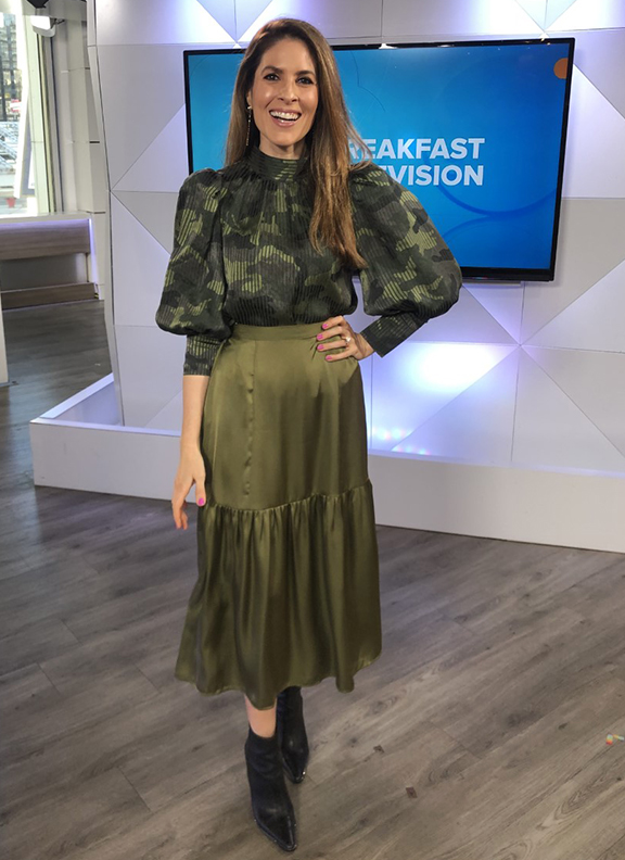 Dina wearing light green skirt with dark green patterned blouse
