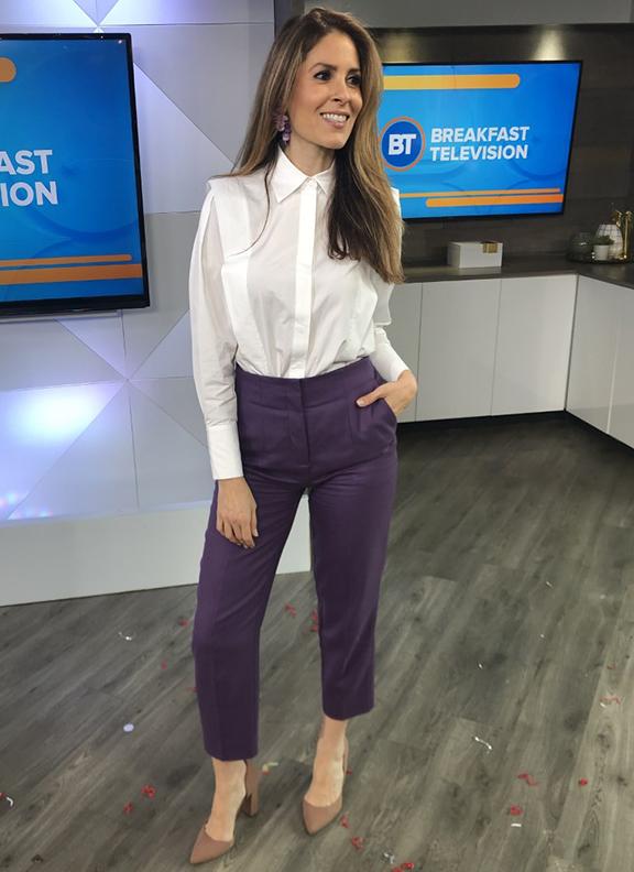 Dina wearing muted purple dress pants with white blouse