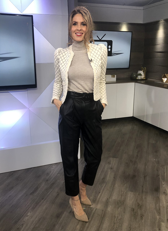 Dina wearing white blazer with beige turtle neck paired with black trousers