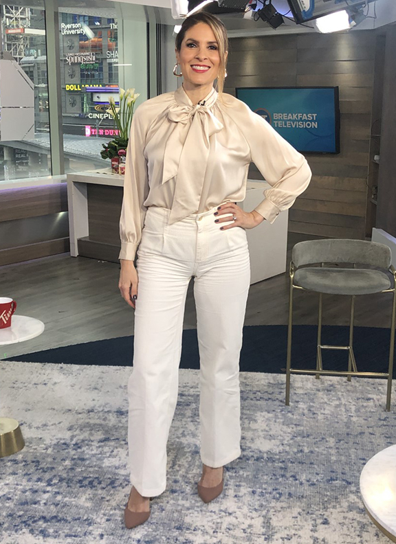 Dina wearing beige satin blouse with white wide leg pants