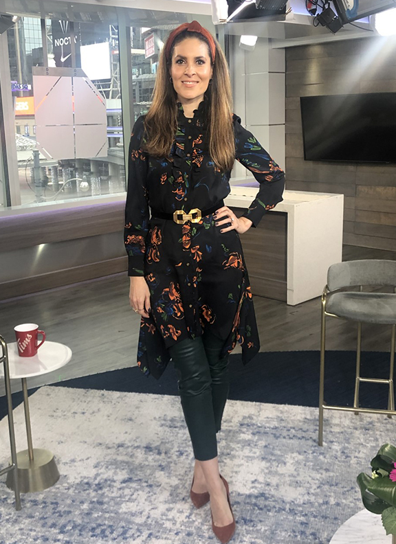 Dina wearing floral printed blouse dress with dark green pants underneath