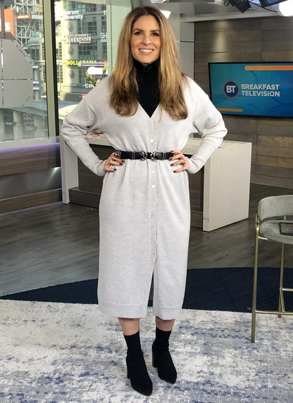 Dina wearing black turtleneck underneath white long cardigan with black booties