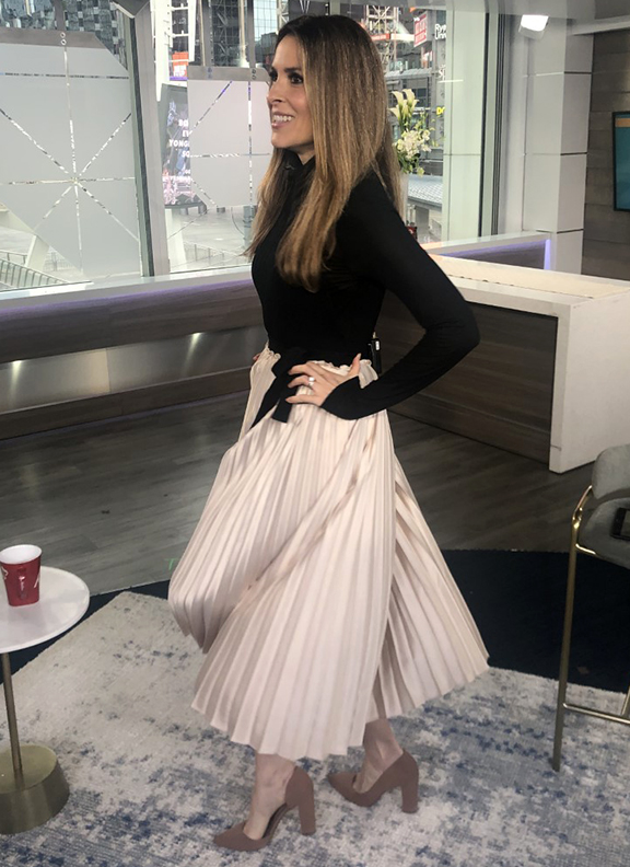 Dina wearing beige pleated skirt with black turtle neck