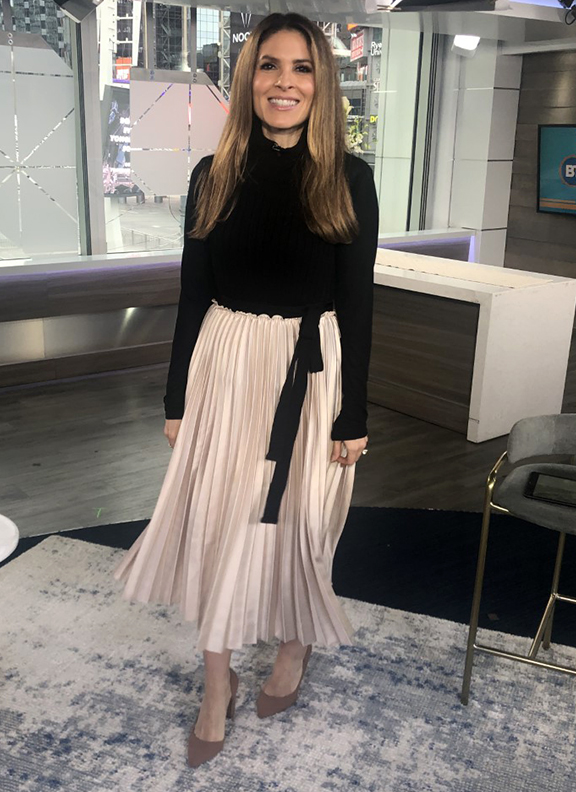 Dina wearing beige pleated skirt with black turtle neck - 2