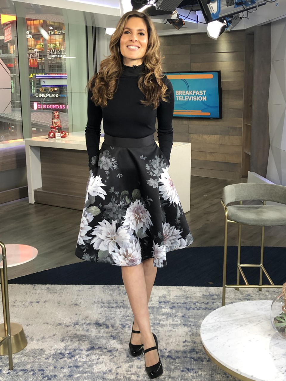 Dina wearing white flower print skirt with black top with heels