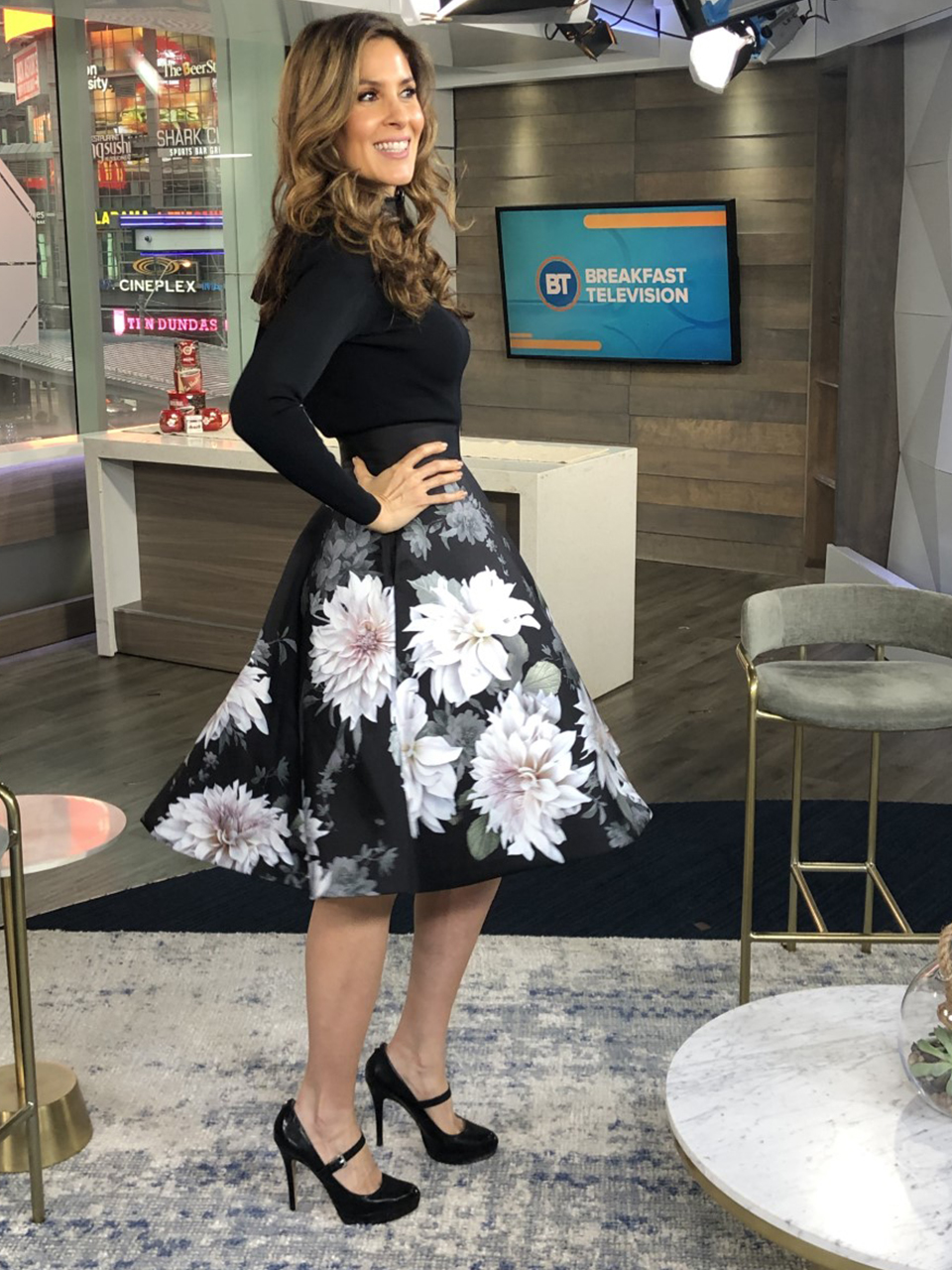Dina wearing white flower print skirt with black top with heels - 2
