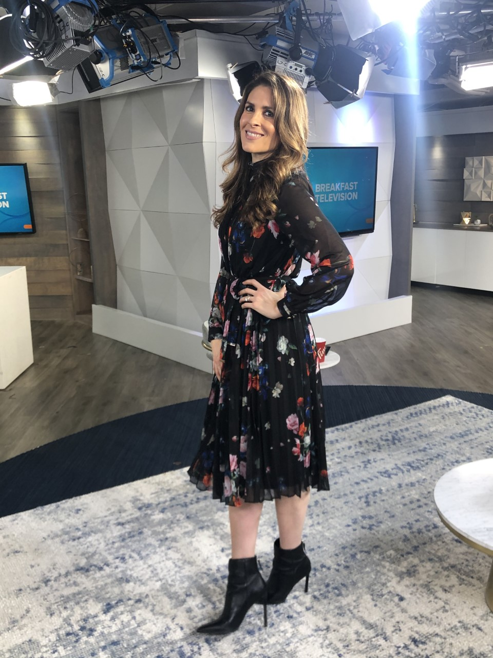 Dina wearing a black floral print dress with black booties