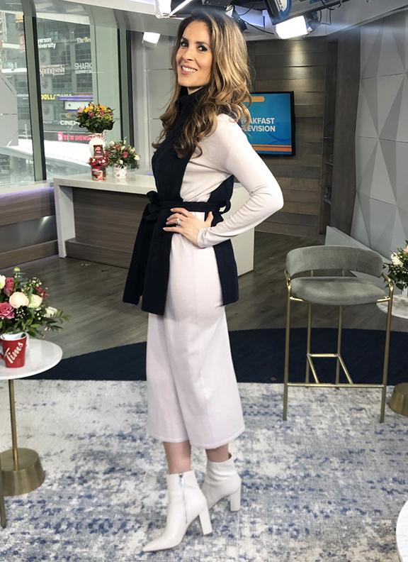 Dina wearing all white ensemble underneath black belted vest